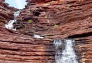 Neal Pritchard: A photo of a large rock formation with water flowing down called Joffery Gorge in Karijini National Park, Western Australia